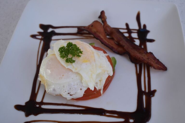 An elegantly plated breakfast consisting of eggs and bacon