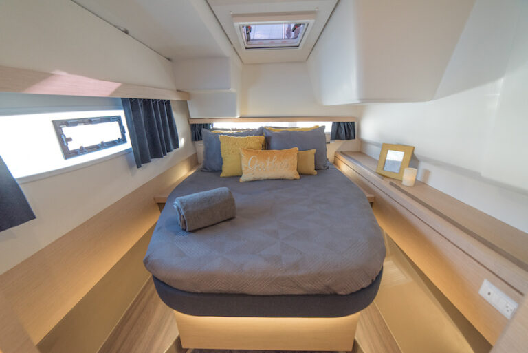 A bed in a sleeping cabin aboard the 3 Sisters yacht, part of the And Beyond Yacht Charters fleet