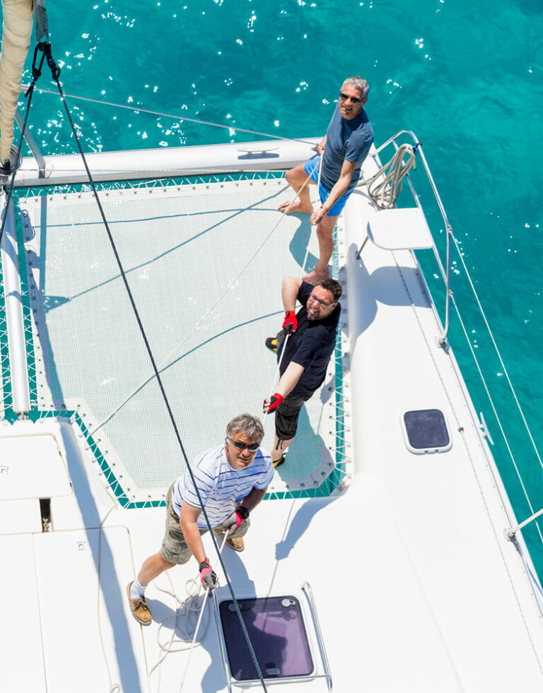 Three yacht crew members pulling on a rope to hoist a sail