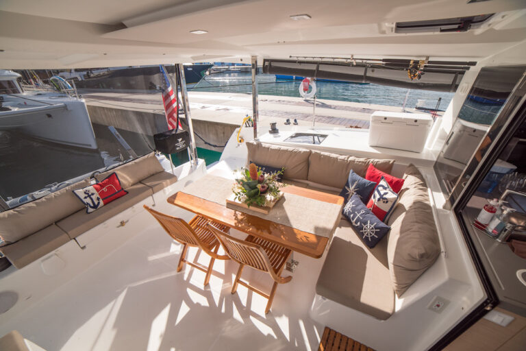 The patio lounge aboard the 3 Sisters private catamaran charter with a dining table and ample seating