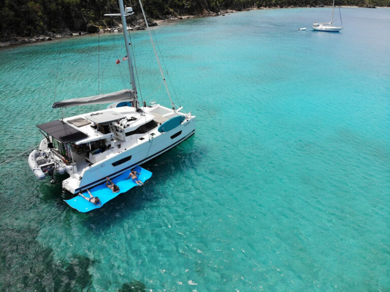 Three Sisters catamaran anchored near a beach with three people floating on a float pad nearby