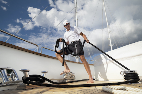 A male crew member tightens the anchor lines on the deck of a private charter yacht