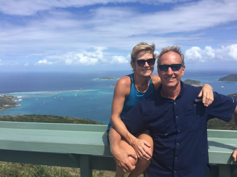 Collin and Corrine, owners of &Beyond Yacht Charters, standing in front of a view of a bay
