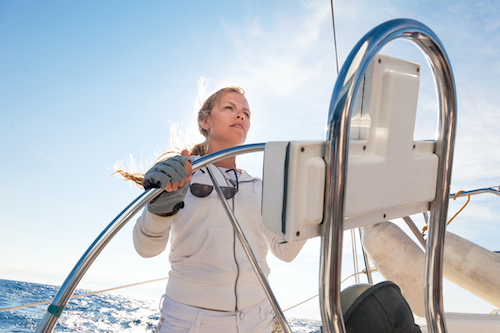 A female yacht crew member steers a yacht during a luxury yacht vacation