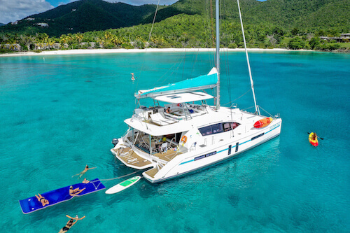 Dolphin Daze yacht in a bay with people swimming and floating on float pads nearby