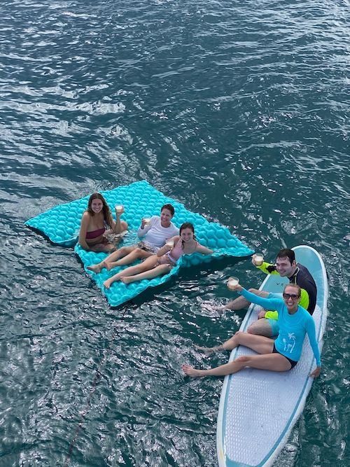 People having drinks while floating on a float pad and a paddleboard in the ocean