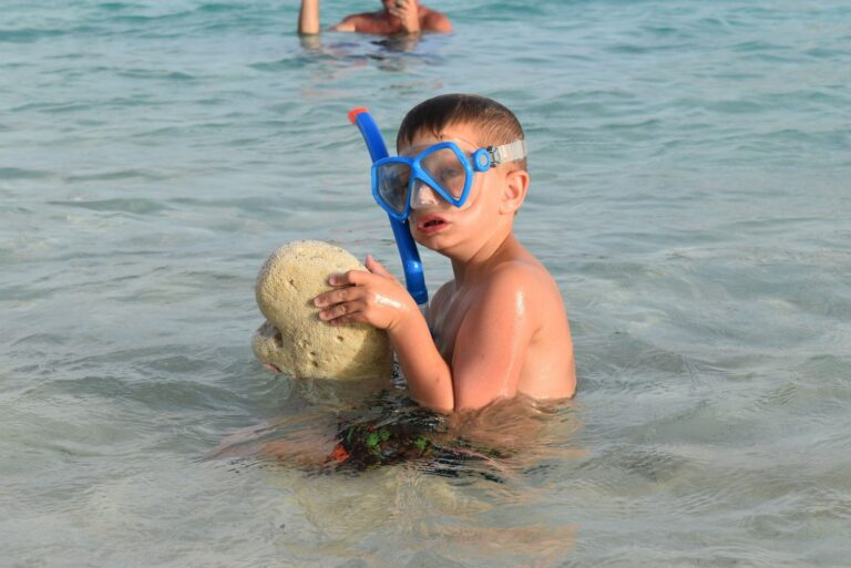 A young boy in a snorkel mask holds a piece of coral while snorkeling in the Virgin Islands