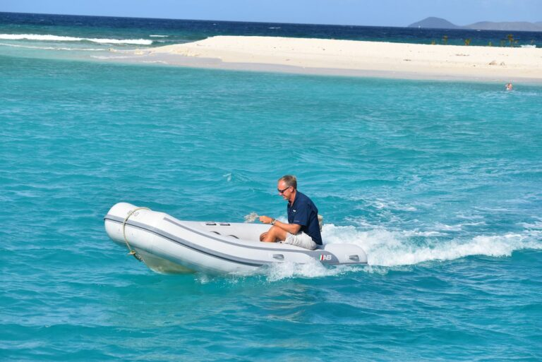 A man drives a speed yacht through blue water with a white sandbar in the background