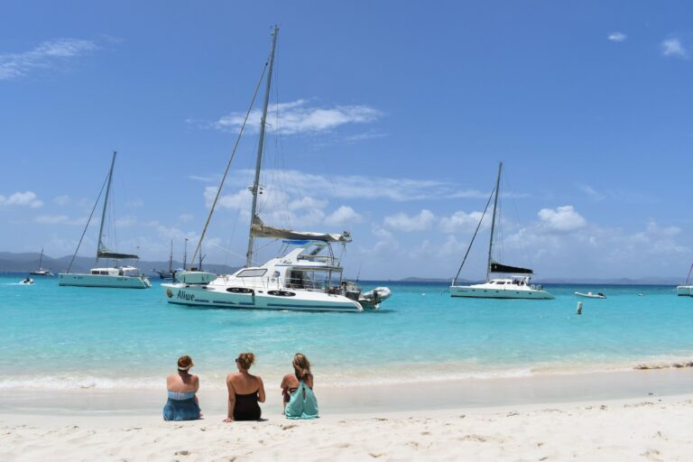 Three women sit on a white sand beach with yachts anchored in the water in the background