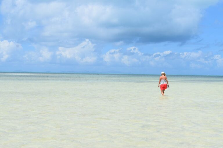 A woman walking through shallow water on a beach in the Virgin Islands