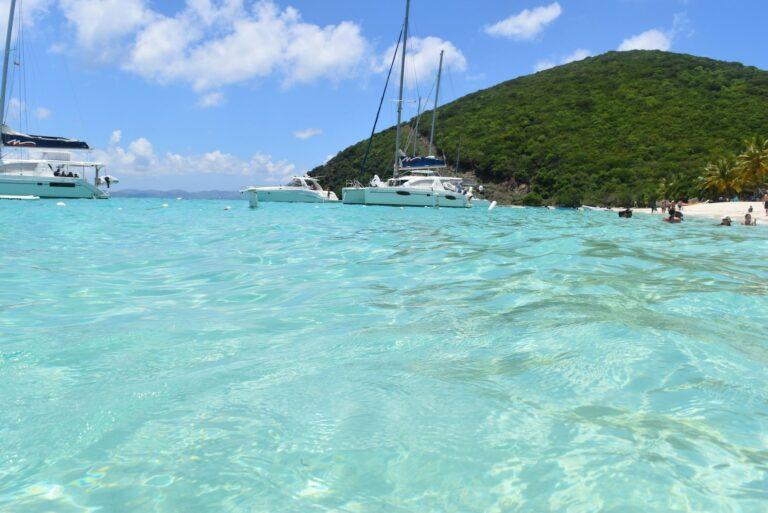 Several yachts anchored near a white sand beach