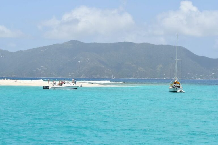 People on a sandbar with several yachts anchored nearby in the Virgin Islands