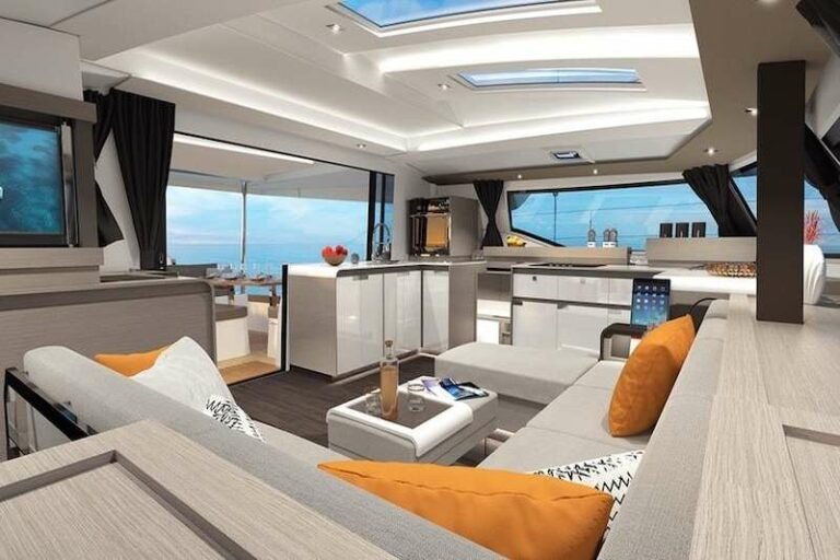 The lounge with sectional seating and the galley in the background aboard the Hero's Journey yacht charter