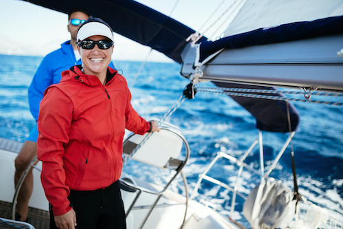 A female yacht crew member stands and smiles near sail rigging aboard a private yacht with a male crew member in the background