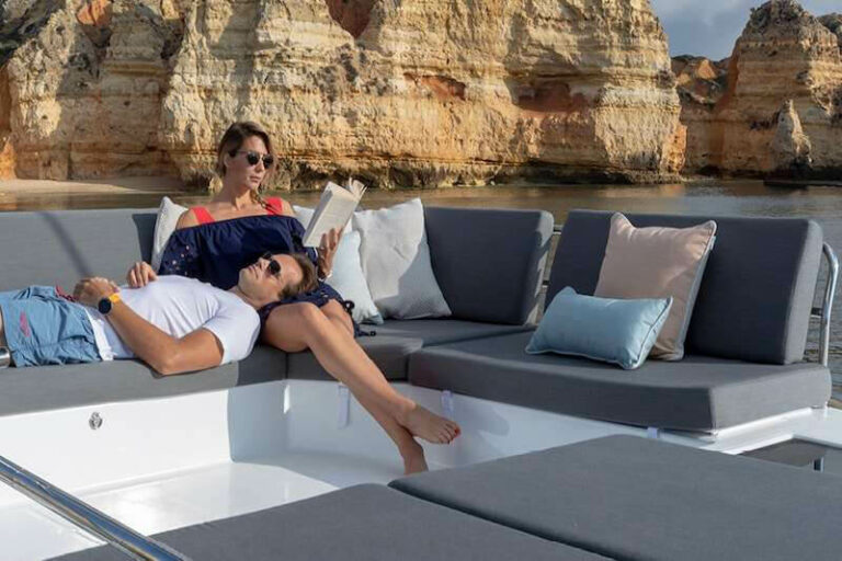 A woman reading a book while a man lays down with his head in her lap on the deck of a yacht
