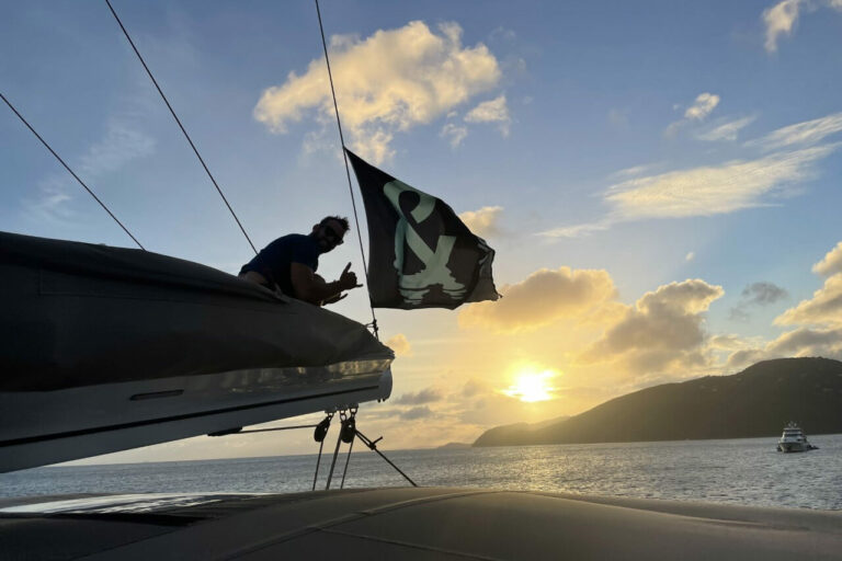 Guest photo of a man on the bow of True Story yacht during sunset