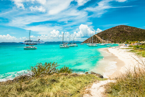 View of White Bay Beach in the British Virgin Islands with a group of catamaran yachts anchored near a white sand beach