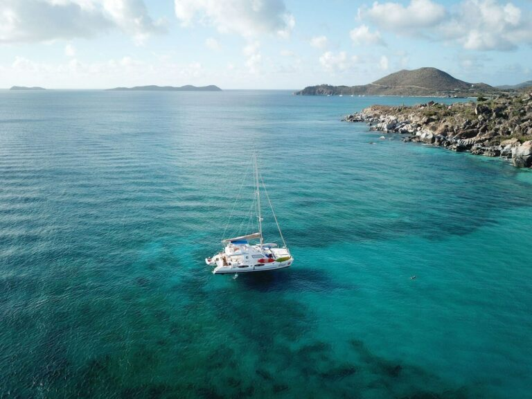 A yacht floats on brilliant blue water near an island shoreline in the Virgin Islands